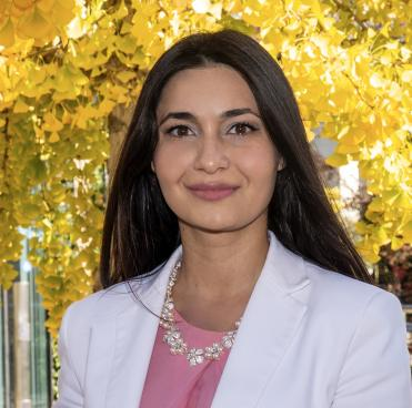 Photo of Betul Ayranci in front of yellow and green tees wearing a white blazer, pink shirt, and jewel necklace