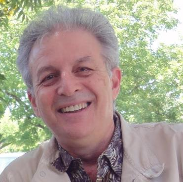 Photo of Charles Amirkhanian smiling in tan jacket and patterned shirt in front of green trees