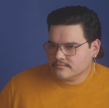Photo of Ruben Zarate in a yellow turtleneck, wire glasses, and earring