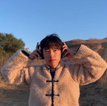 Photo of Vincent Tran in a fuzzy coat against a blue sky holding earphones to their head