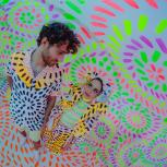Fish eye photo of the Magdalena Bay duo standing in outfits covered in neon dashes with a backdrop to match